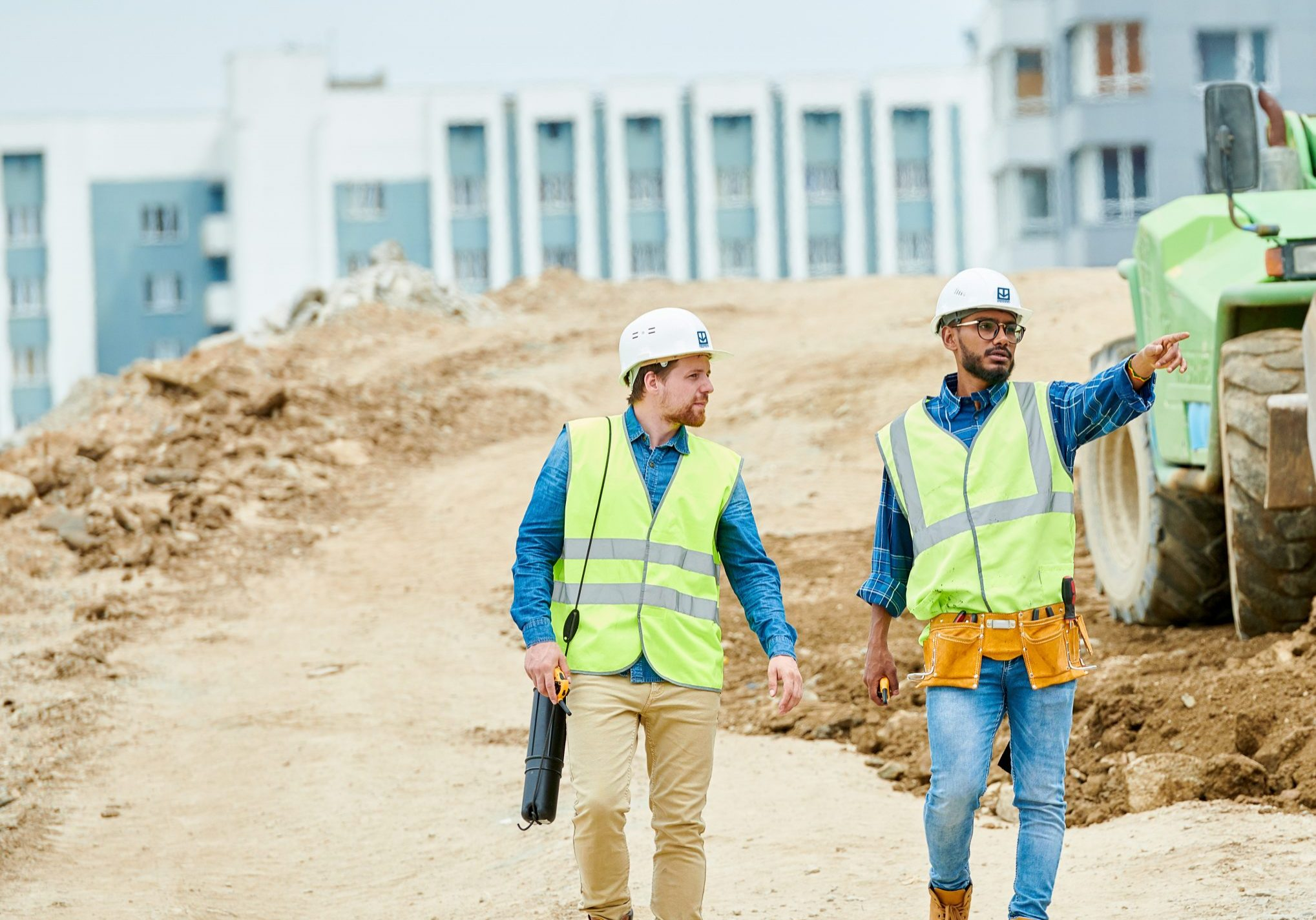 Two guys in helmets and waistcoats walking near digger and pointing at distance during inspection on construction site